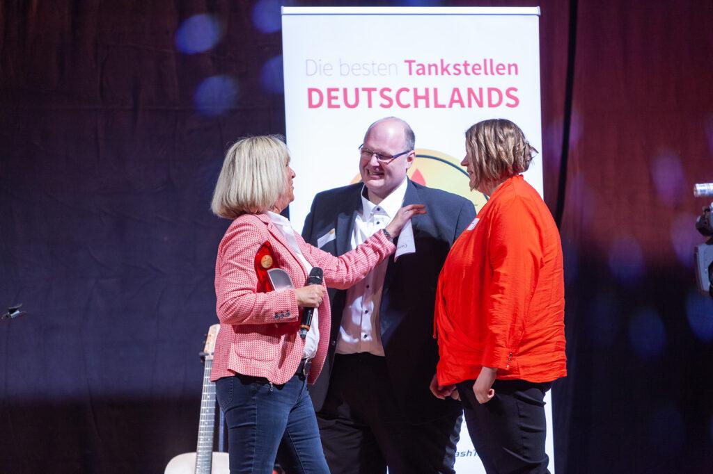 """Thomas Lex und seine Lebensgefährtin Sara Ostermöller nehmen aus den Händen von Laudatorin Sylvia Reyers die Auszeichnung in der Kategorie """"Shop über 100 qm"""" entgegen."""